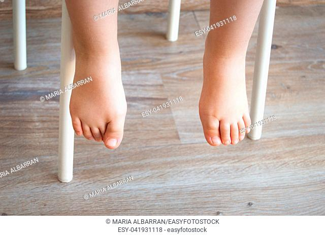 Feet of a child sitting in a chair. Natural lighting