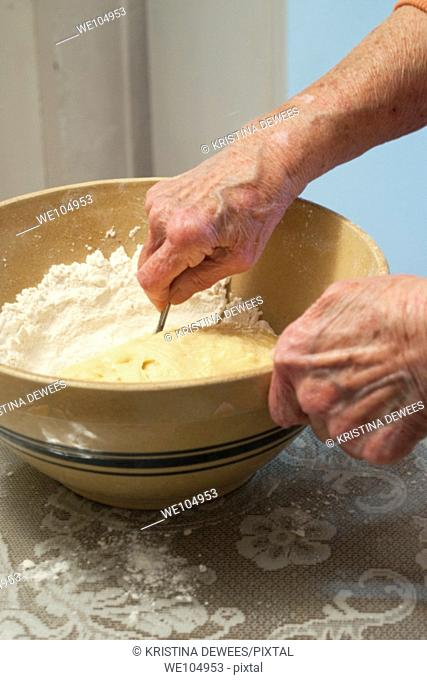 An old woman stirring cookie dough