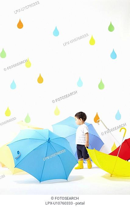 Boy Surrounded by Umbrellas in Rain