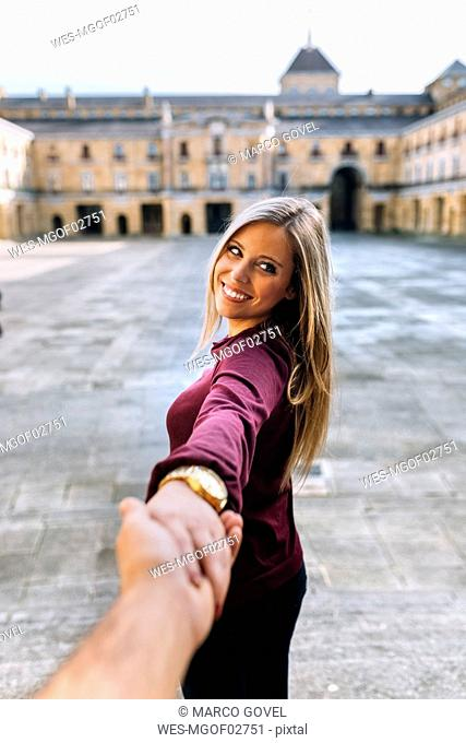 Happy young woman holding hand on urban square