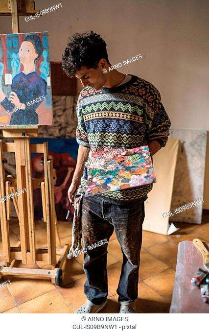 Male artist holding palette in artists studio