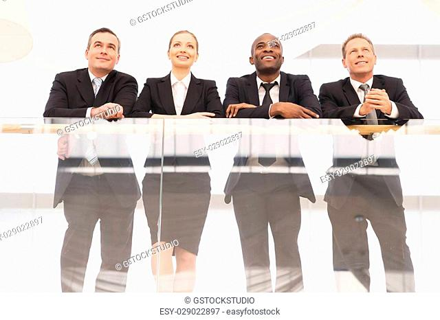 Business team. Low angle view of four confident business people standing close to each other and smiling
