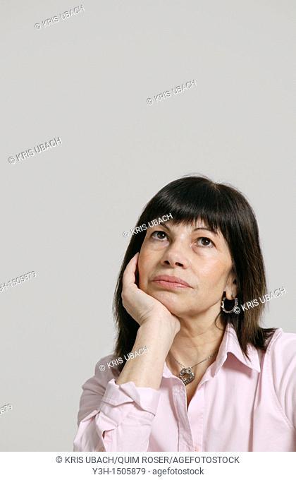 Studio shot of woman, hand of chin