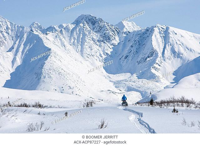 A lone snowmobiler travels through the McKenzie Mountains along the North Canol Trail. North Canol Trail, Yukon Territory