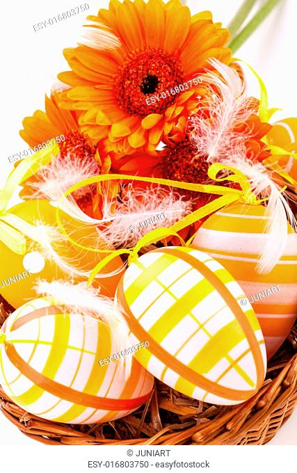 Colourful yellow hand decorated traditional Easter eggs with stripes and polka dot patterns arranged with colourful orange Gerbera daisies a decorative ribbon