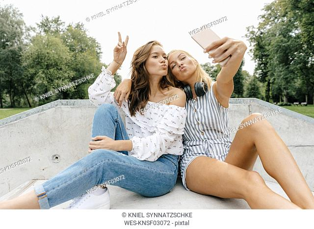 Two happy young women taking a selfie in a skatepark