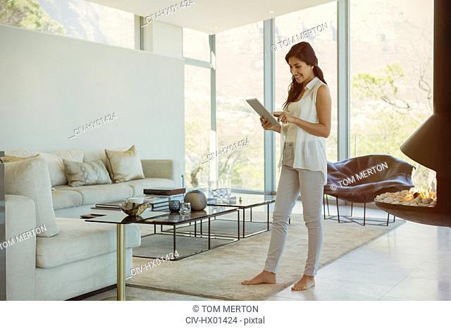 Woman using digital tablet in luxury living room