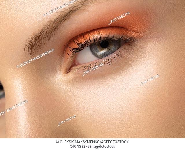 Closeup of a young beautiful woman eye with orange makeup