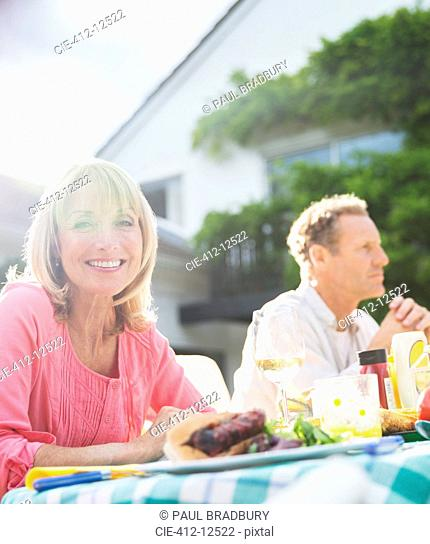 Smiling woman at table in backyard