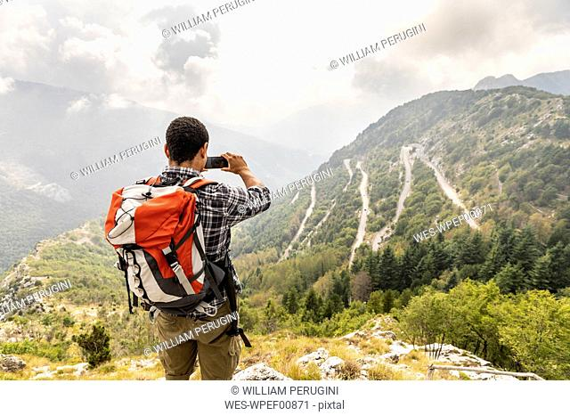 Italy, Massa, man hiking and taking a picture of the view in the Alpi Apuane