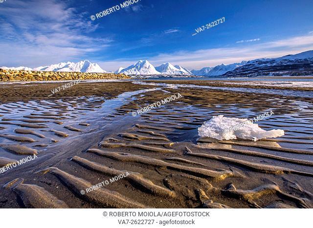 The icy sandy beach surrounding the snow capped mountains Breivikeidet Lyngen Alps Tromsø Lapland Norway Europe