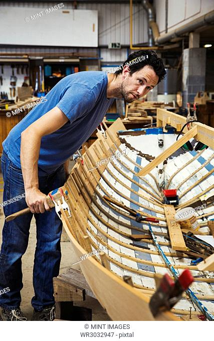 Man standing in a boat-builder's workshop, working on a wooden boat hull