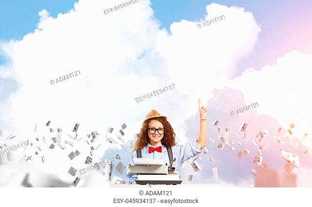 Young and beautiful woman writer in hat and eyeglasses using typing machine and pointing upside while sitting at the table among flying papers with cloudy...