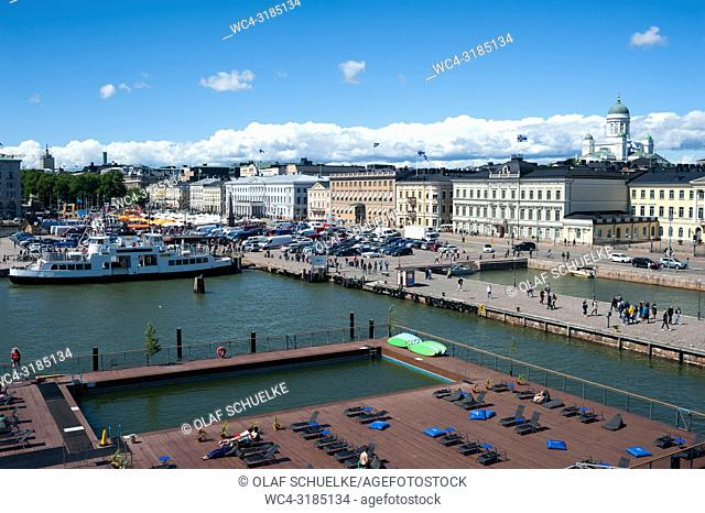 Helsinki, Finland, Europe - An elevated view of the Allas Sea Pool terrace with the harbour, the central market square and the Presidential Palace in the...