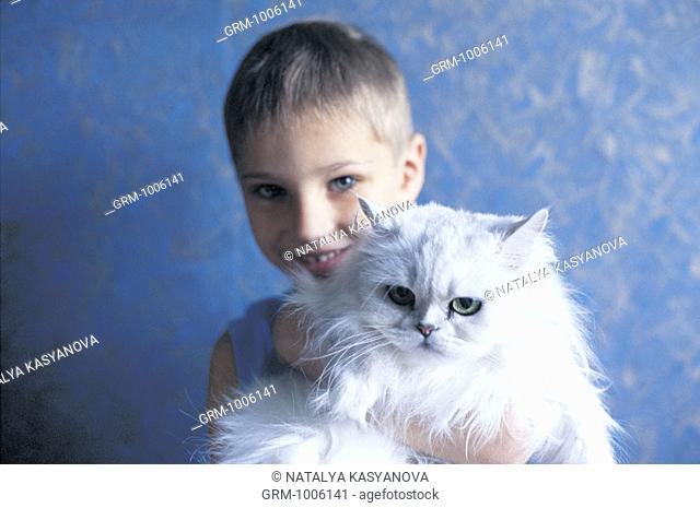 Young child holding white Persian cat