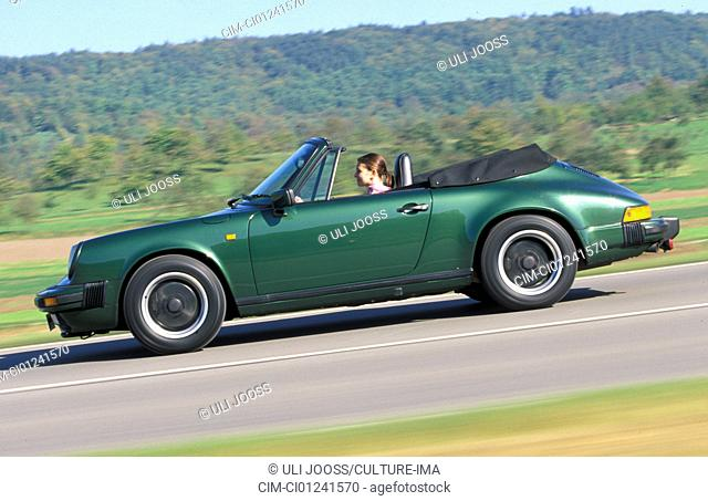 Car, Porsche 911 SC Convertible, model year 1983-1989, this vehicle: model year 1985, open top, dark green, FGUJ, driving, side view, country road