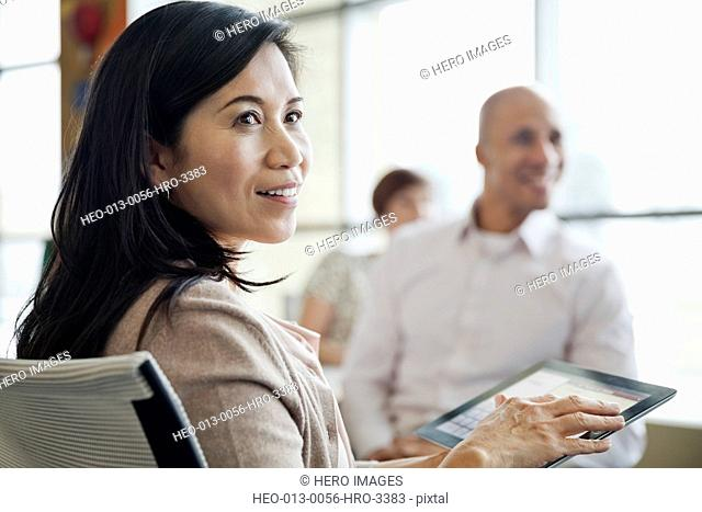 Businesswoman holding digital tablet with colleagues in conference room