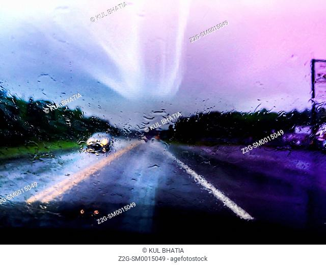 One car drives on a highway in wet, stormy conditions, Ontario, Canada
