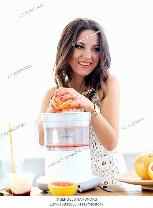 Natural, vitamins. Cute, attractive woman making orange juice
