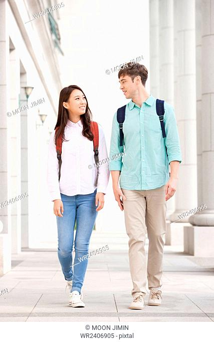 College girl and a male international student walking on campus together and looking at each other with a smile