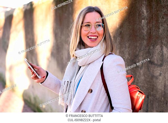 Female higher education student by sunlit wall looking over her shoulder
