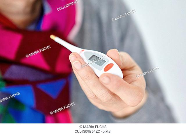 Senior woman holding digital thermometer, close-up