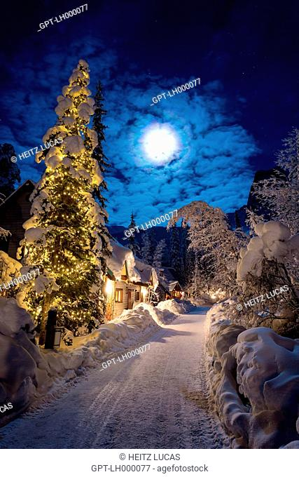 NIGHT SHOT OF LIT-UP CHALETS AND PINE TREE WITH CHRISTMAS GARLAND, FULL MOON, EMERALD LAKE LODGE, BRITISH COLUMBIA, CANADA