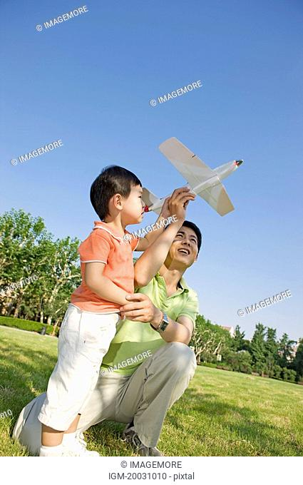 Family, father and son playing toy airplane