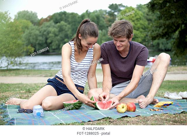 Young couple having picnic, cutting watermelon