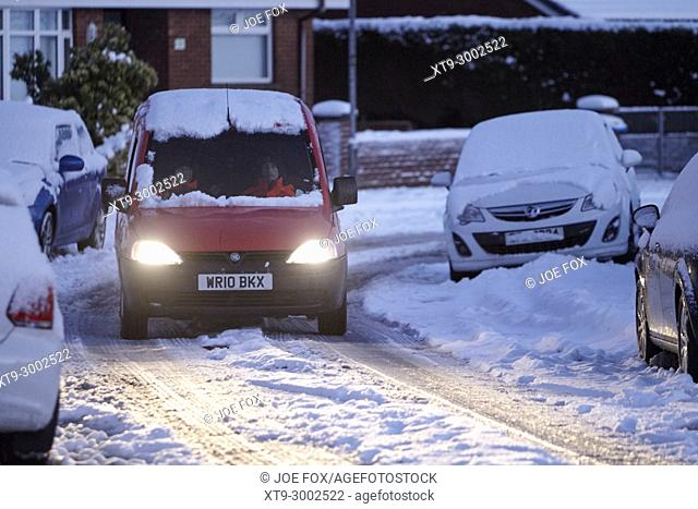 postmen driving royal mail van along street covered in snow in newtownabbey northern ireland