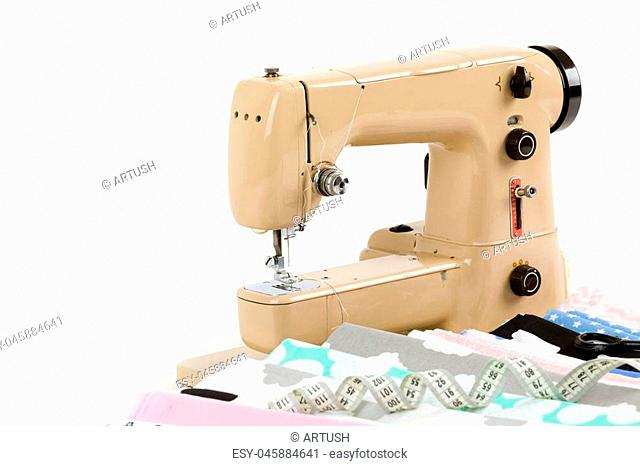 Sewing machine, cotton fabric and tailor measurement tape isolated on white