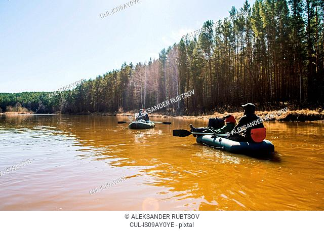 Group of friends rowing dinghies on river