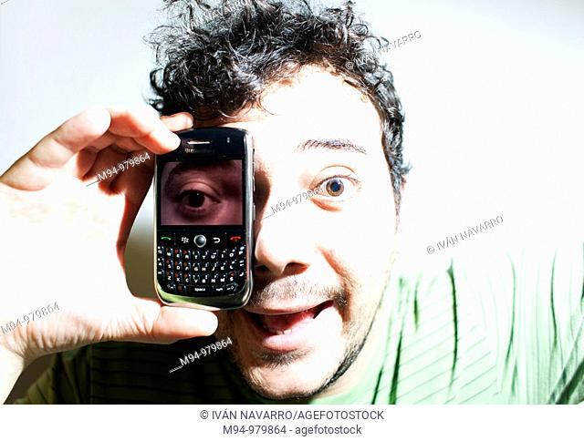 Man with a mobile phone with a photography of his eye