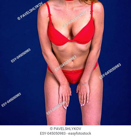 Pretty Slim woman in red lingerie on blue background