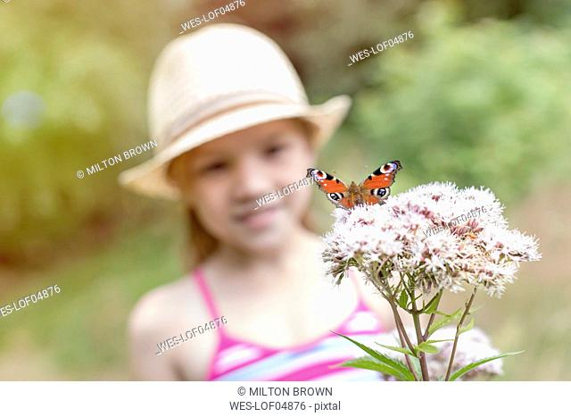 Butterfly on flower with girl in background