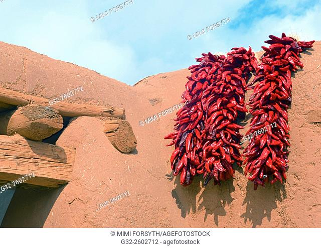 Red chile ristras on adobe wall, La Cienega, New Mexico, USA