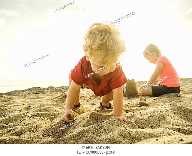 Girl (4-5) and boy (2-3) playing on beach