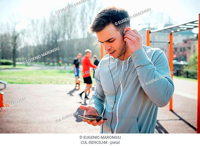 Calisthenics class at outdoor gym, young man putting in earphones