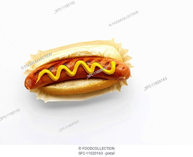 A hot dog with mustard on a paper plate