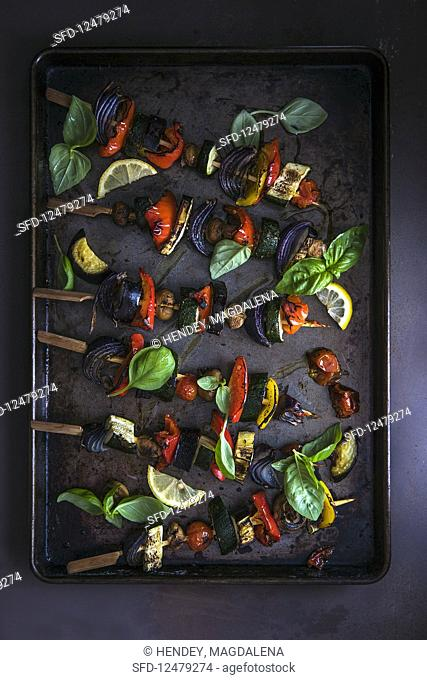 Vegetables kebabs on a baking tray with fresh basil and lemon