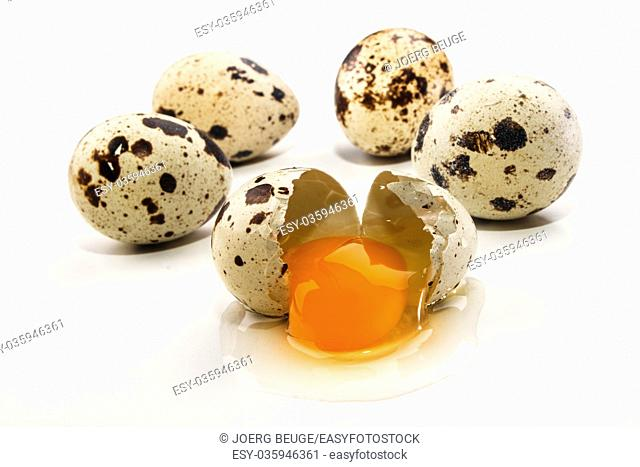some quail eggs and an open egg on bright background