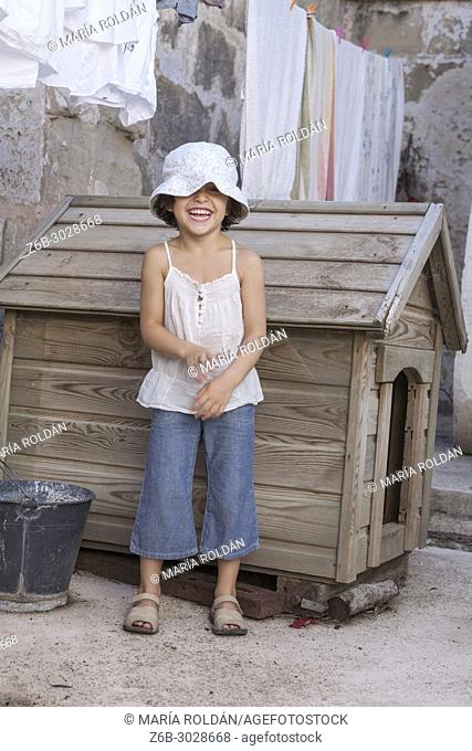 happy little girl outdoors in frot of a doghouse