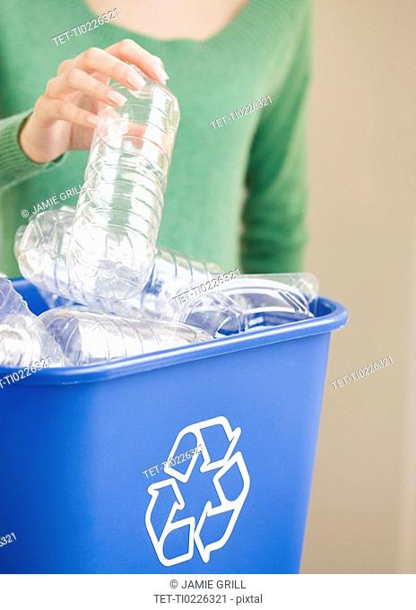 Woman filling recycling bin