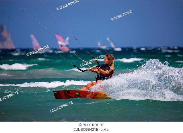 Young woman kite surfing at speed, Majorca, Spain