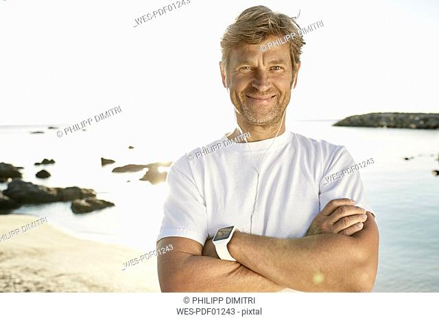 Portrait of smiling mature man with smartwatch and earphones on the beach