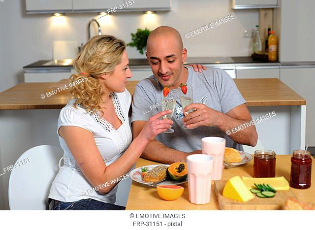 Happy couple clinking champagne glasses in kitchen