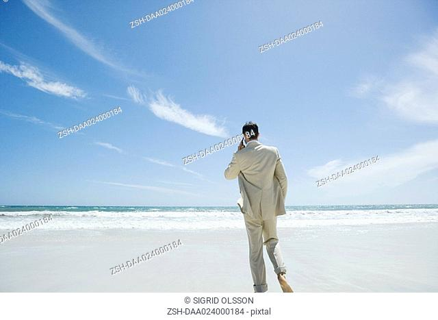 Businessman walking barefoot on beach, using cell phone