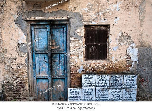 Dilapidated facade of a house with religious inscriptions, Vrindavan, Uttar Pradesh, India