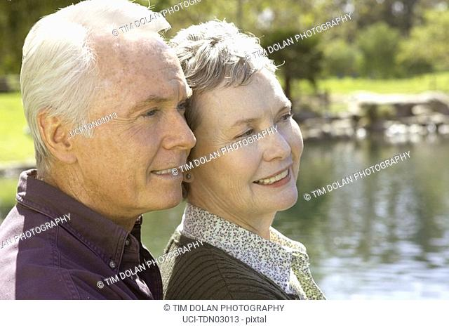 Senior couple standing by pond