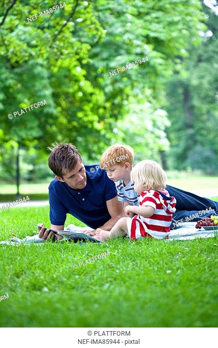 Mid adult father reading book to children